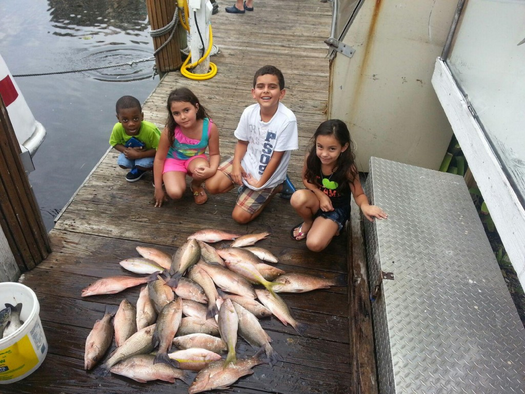 Kids at the dock with their snapper catch