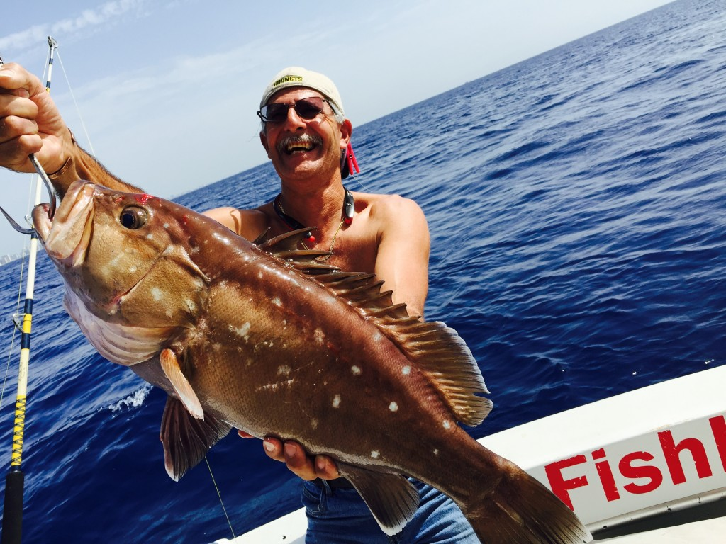 Happy fisherman posing with a snowy grouper