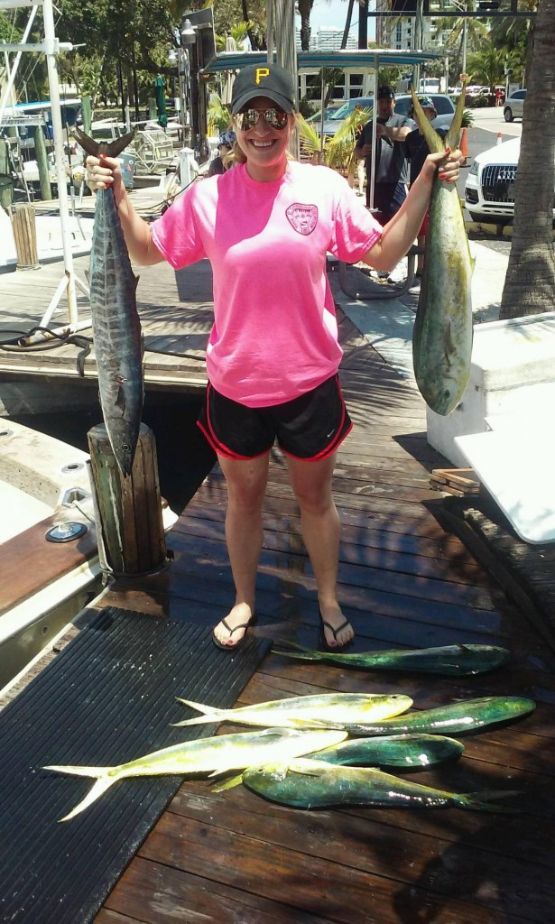 Fisher gal holding a wahoo and dolphin and more dolphin laying at her feet at the dock