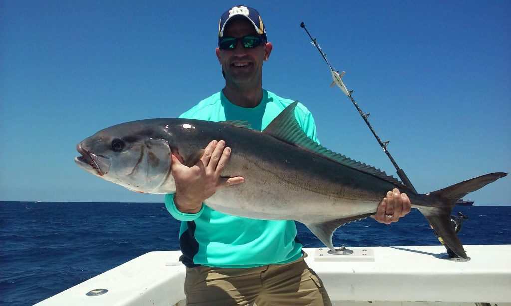 Exhausted angler holding a big amberjack just brought up from the deep