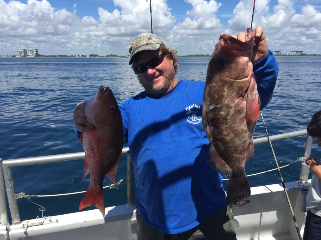 Capt Billy holding a mutton and grouper aboard the Catch My Drift