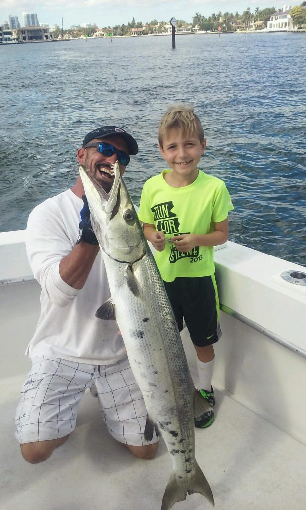 Kid with a giant barracuda in the boat.