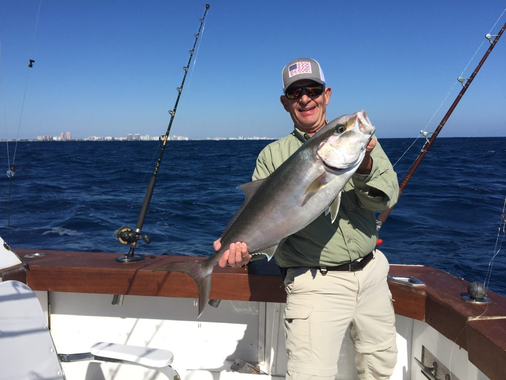 Happy fisherman holding a nice amberjack