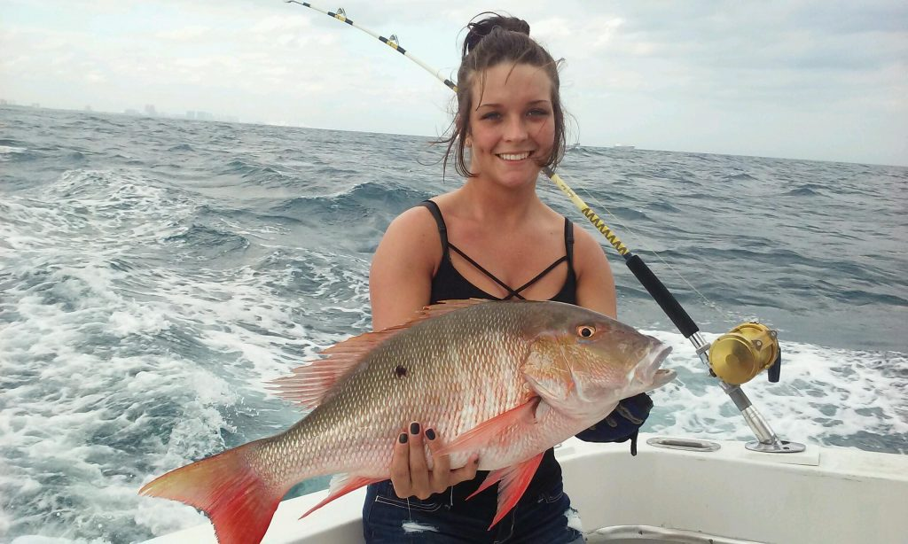 Pretty girl holding a big mutton snapper she just caught on our fishing charter.