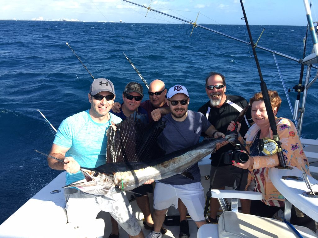 Sailfish being held by a fishing family.