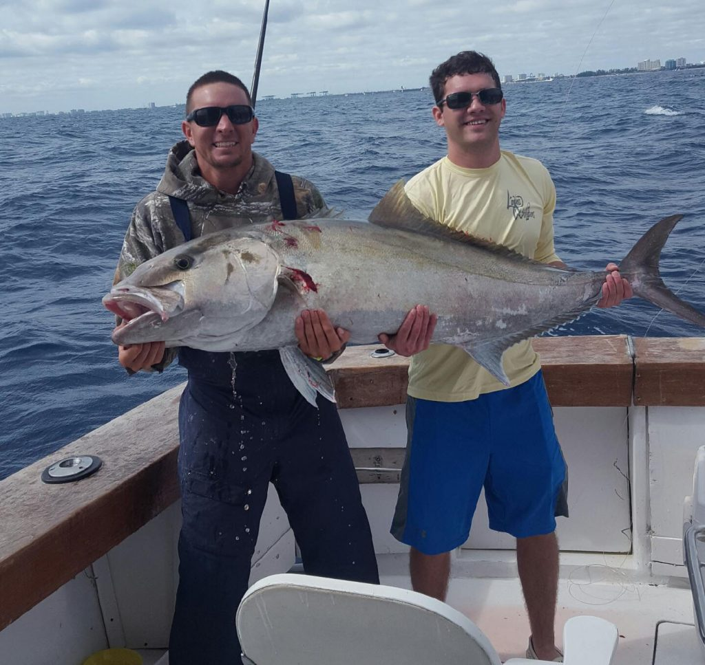 2 guys holding a beast of an amberjack just caught.