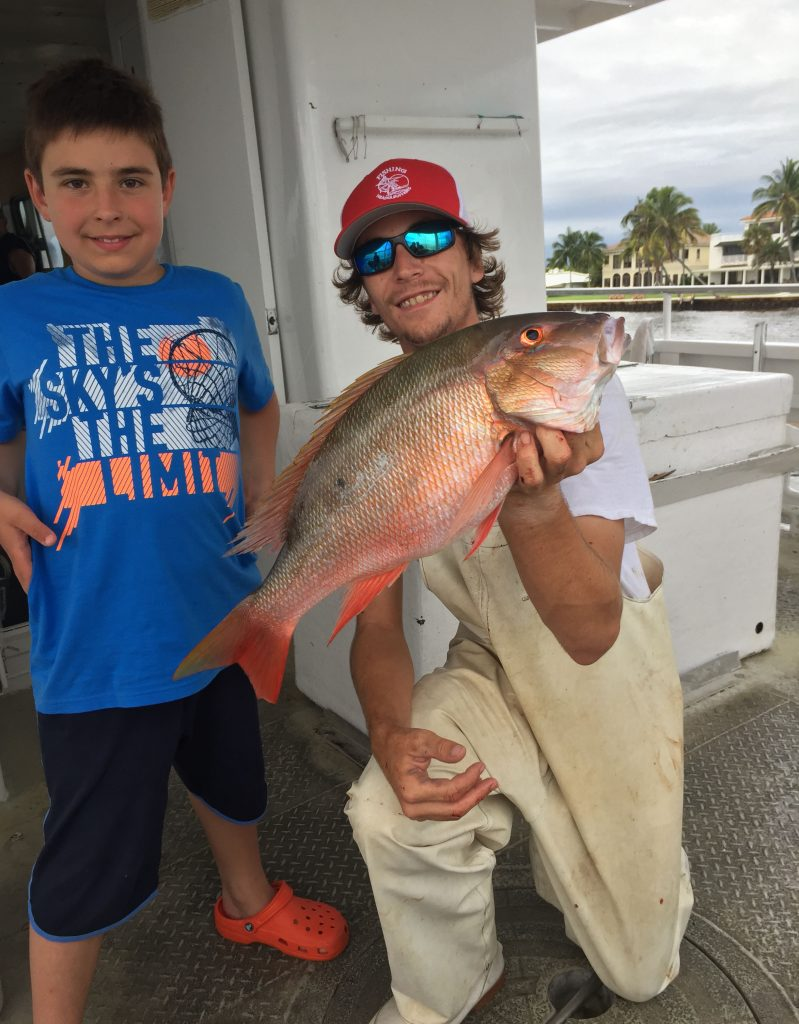 Kyle holding a mutton snapper next to the kid that caught him aboard the Mary B III drift fishing boat.