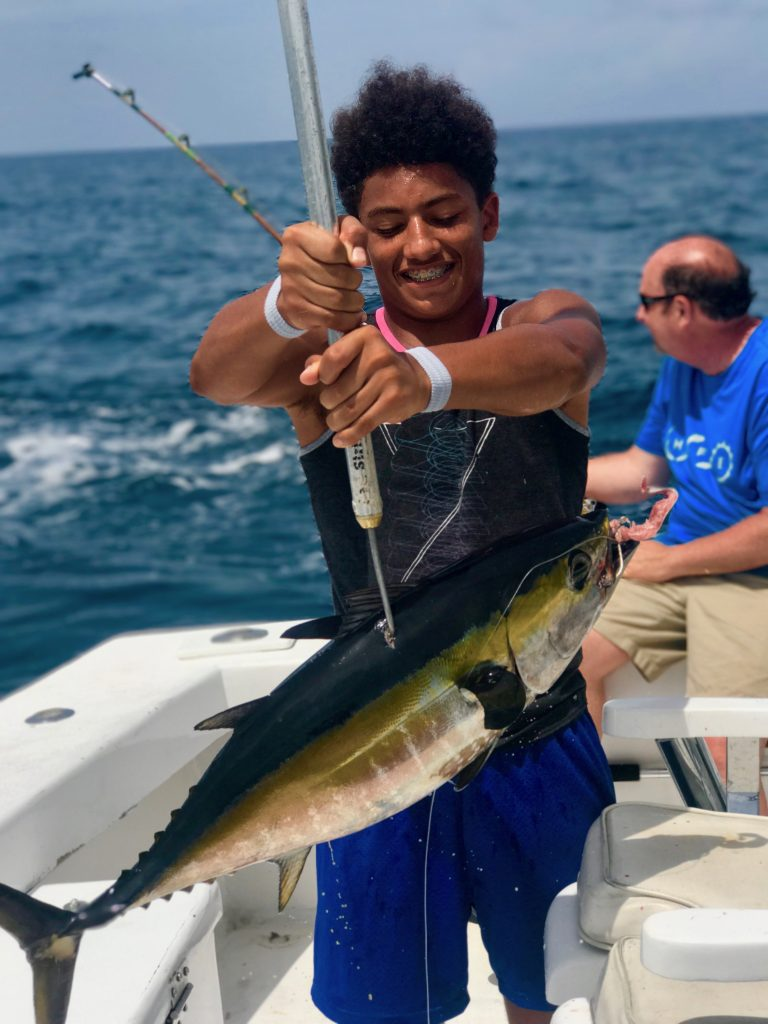 Teenager holding a blackfin tuna on the gaff freshly brought out of the water.