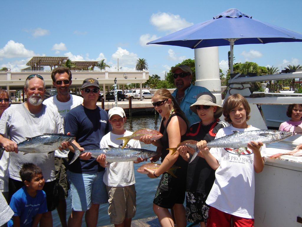 Anglers after their deep sea fishing trip holding their catch at the dock.