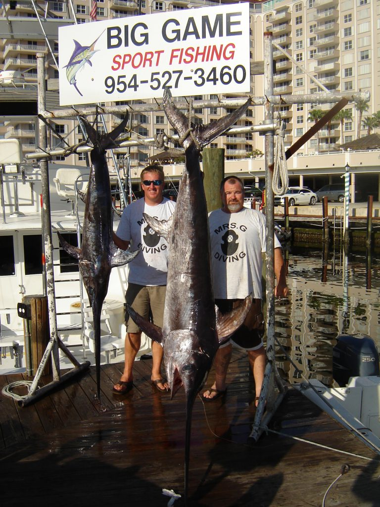 Guys posing with two swordfish they just caught on a night swordfishing charter