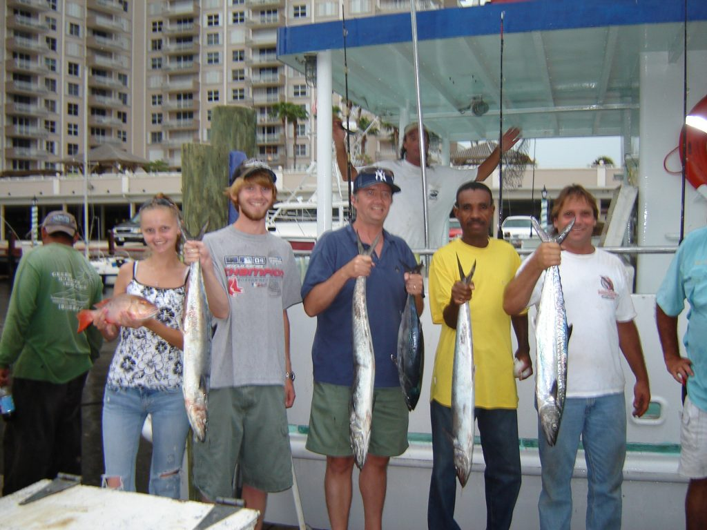 A group holding their fish up after the trip.
