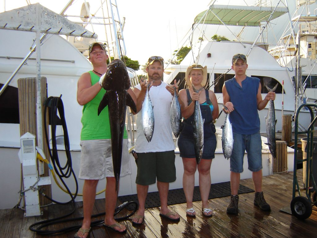 Family holding up their fish after their fishing trip, one guy holding a 5ft cobia