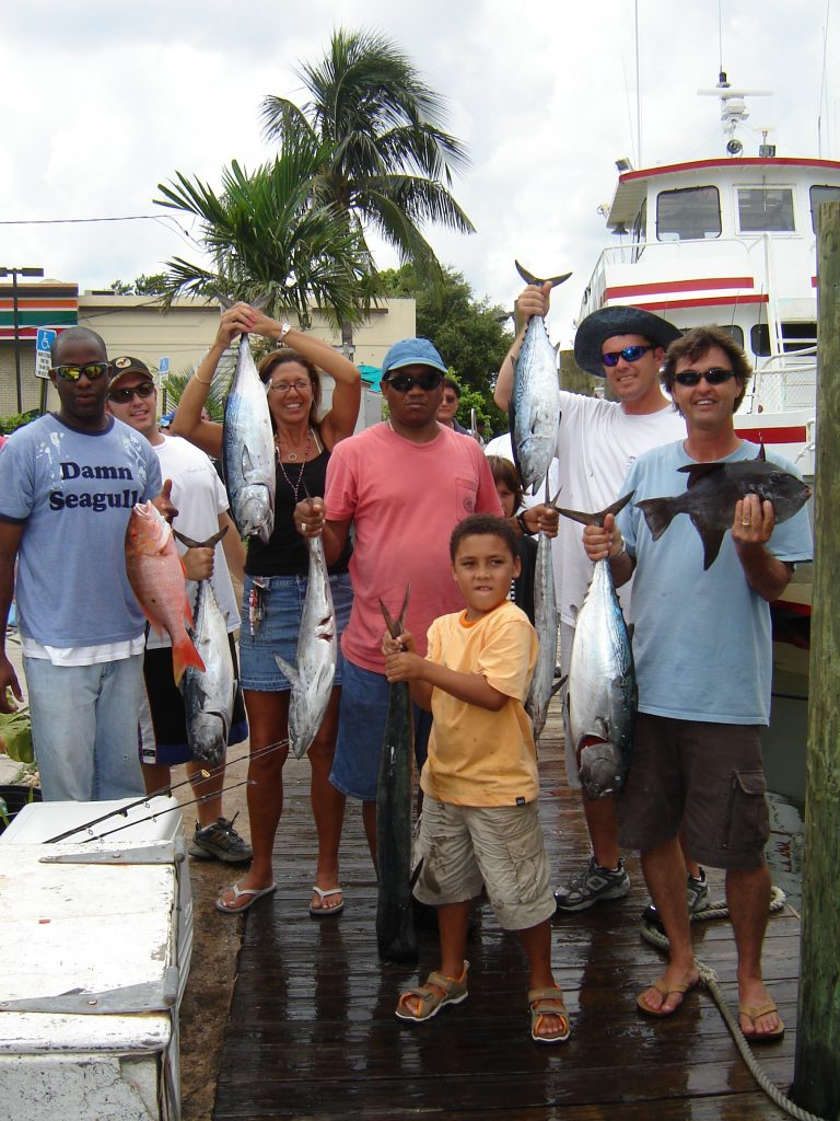 Happy customers holding up their catch in front of our drift fishing boat.