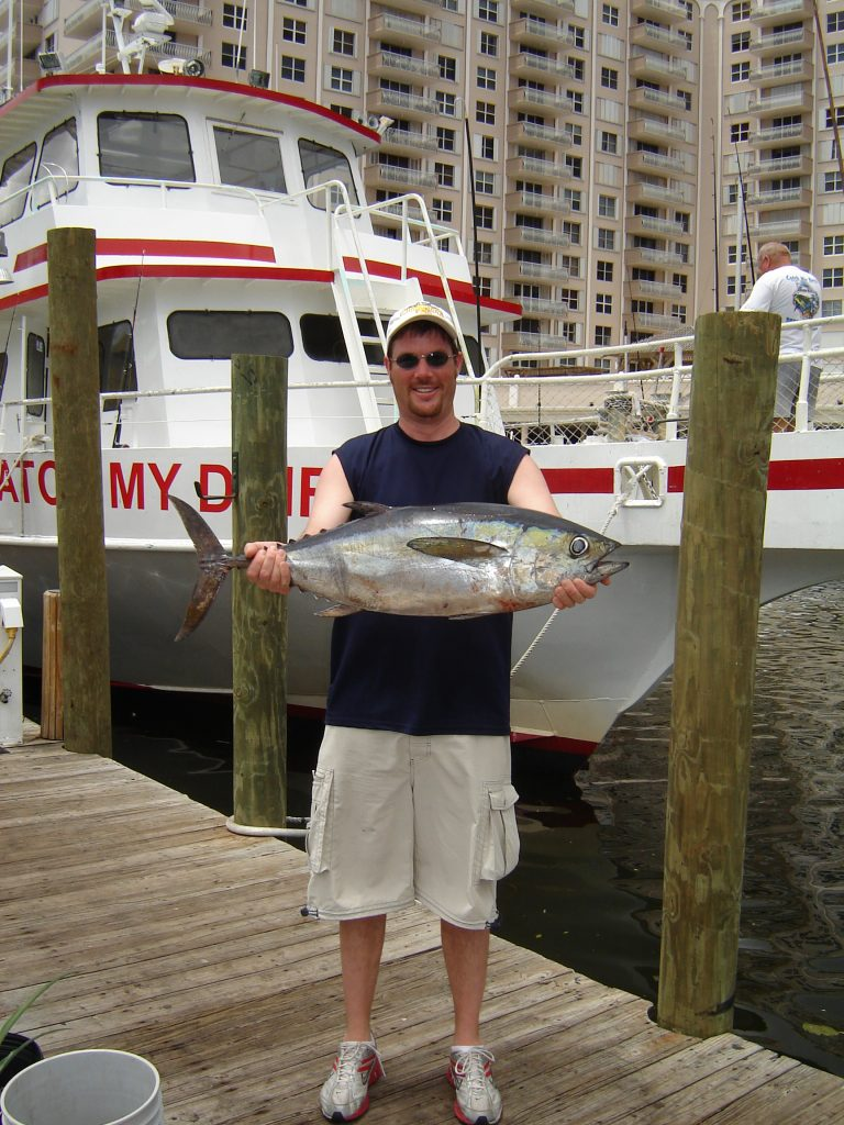 Proud angler posing with a blackfin tuna he caught on a head boat fishing trip in Ft Lauderdale