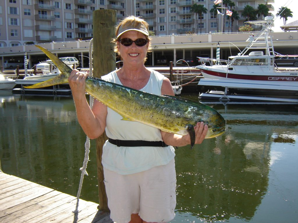 Happy lady holding her dolphin that she caught on our drift fishing trip