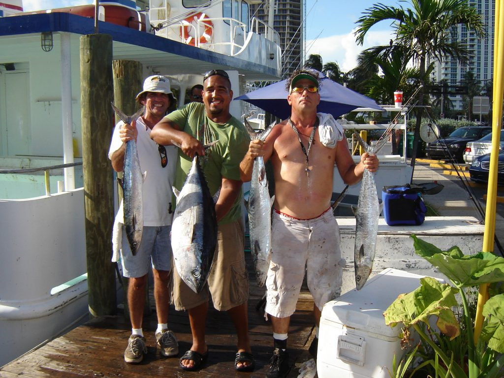 a few guys on our party boat fishing trip holding their fish up.