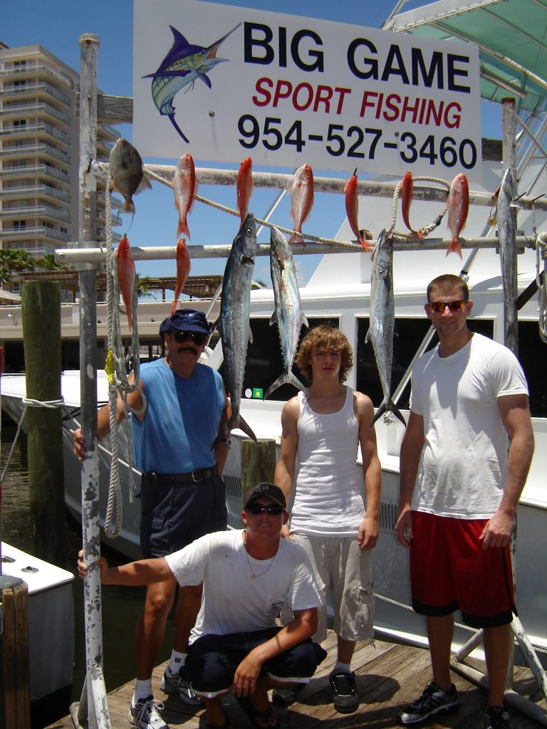Folks posing with their fish after their deep sea charter fishing trip