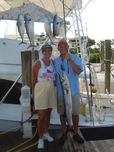 Couple on their honeymoon fishing trip holding a big barracuda they just caught