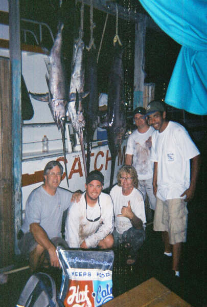 These guys are so happy kneeling under the 5 swordfish they just caught sword fishing that night