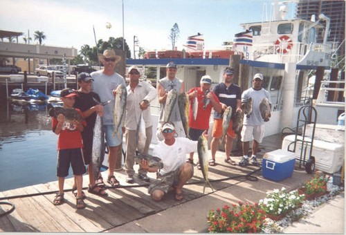 Group holding up their catch at the dock... lots of mahi mahi