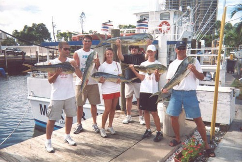 Group of happy fishermen posing with a bunch of dolphin they caught.