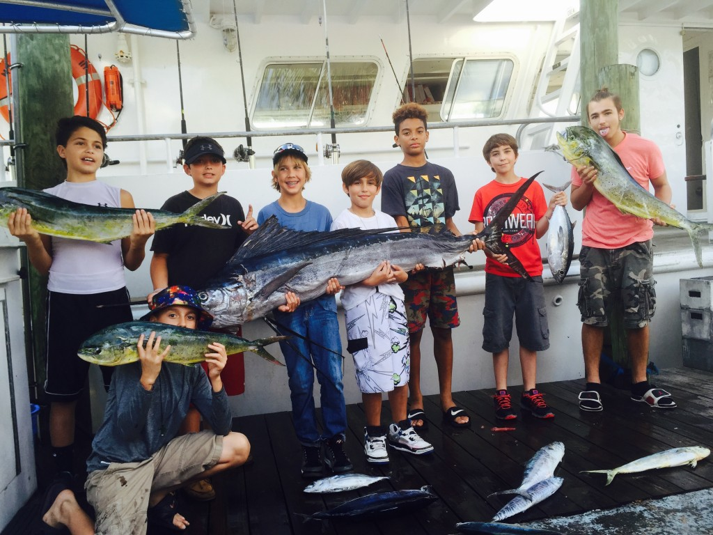 Kids holding sailfish and dolphin at the dock