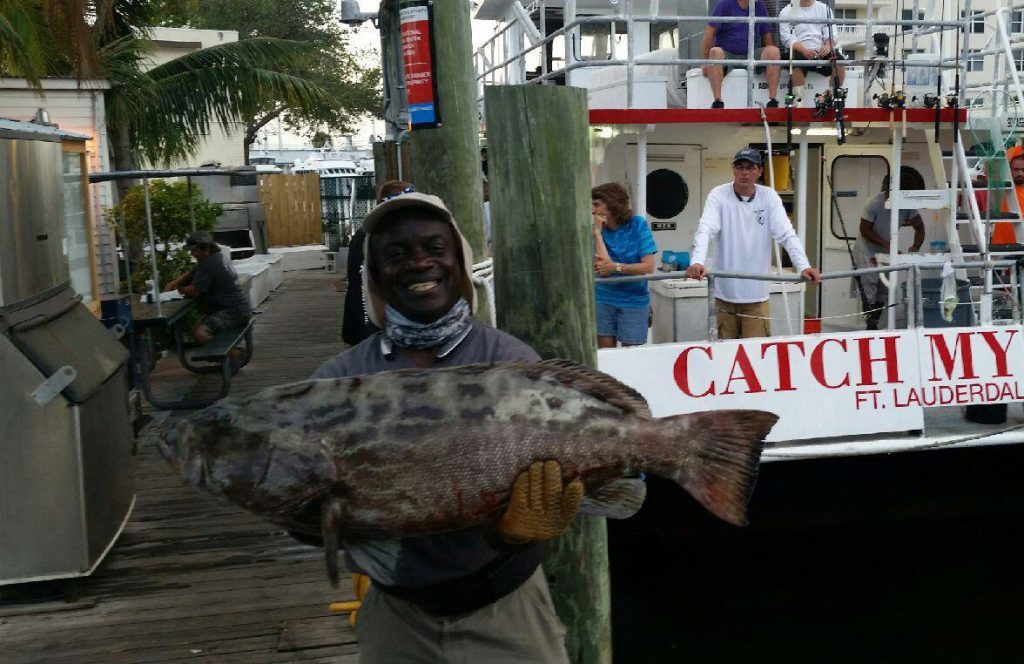 Leslie holding a monster black grouper behind the Catch My Drift