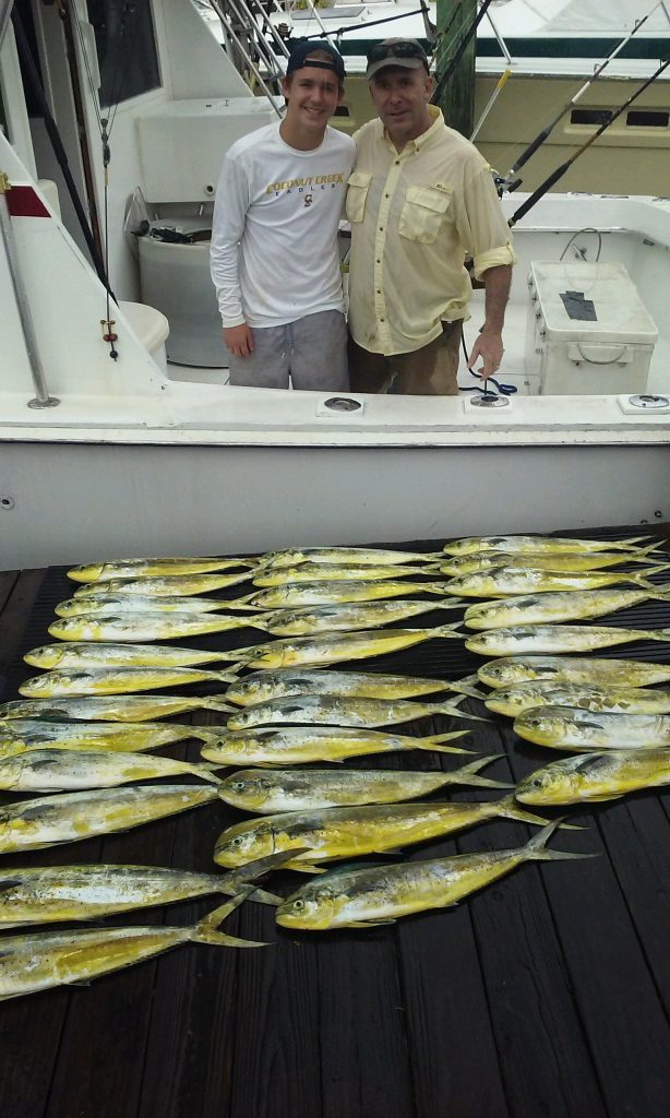 Father and son with a boatload of mahi-mahi caught on our sportfishing charter.
