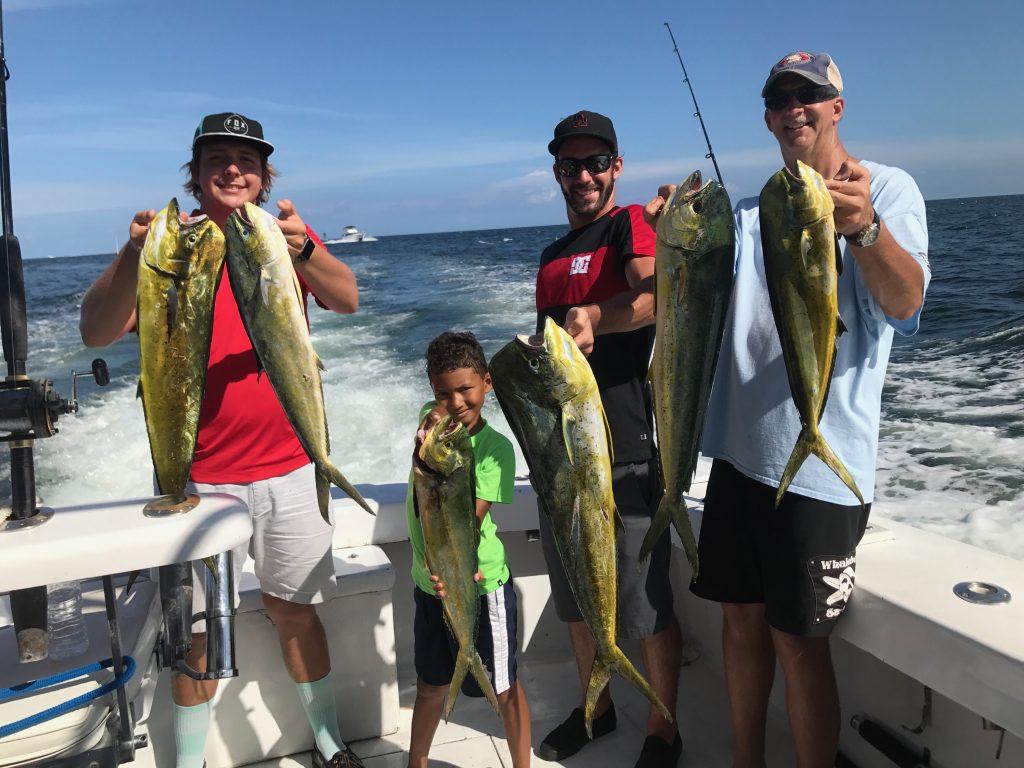 The boys out on the boat holding a nice bunch of good sized mahi-mahi.