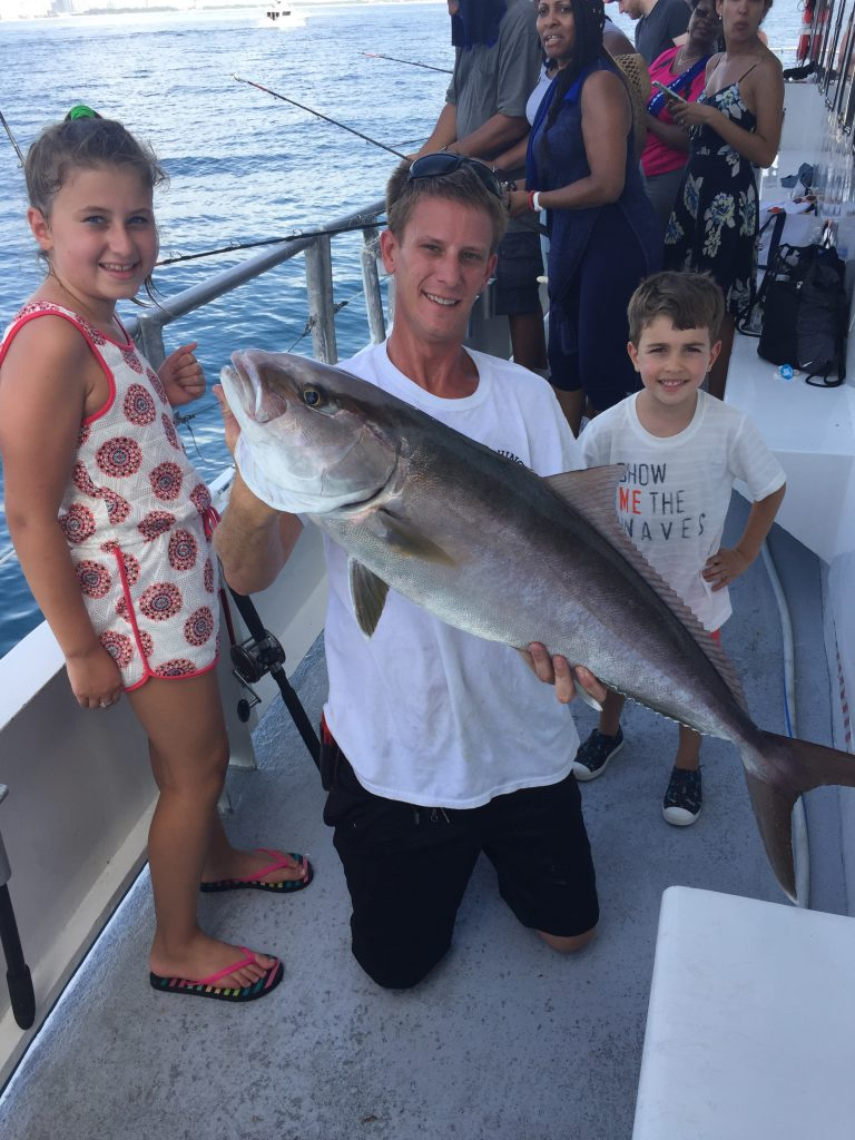 Capt Chris holding a big amberjack next to the 2 kids who caught it on the boat.
