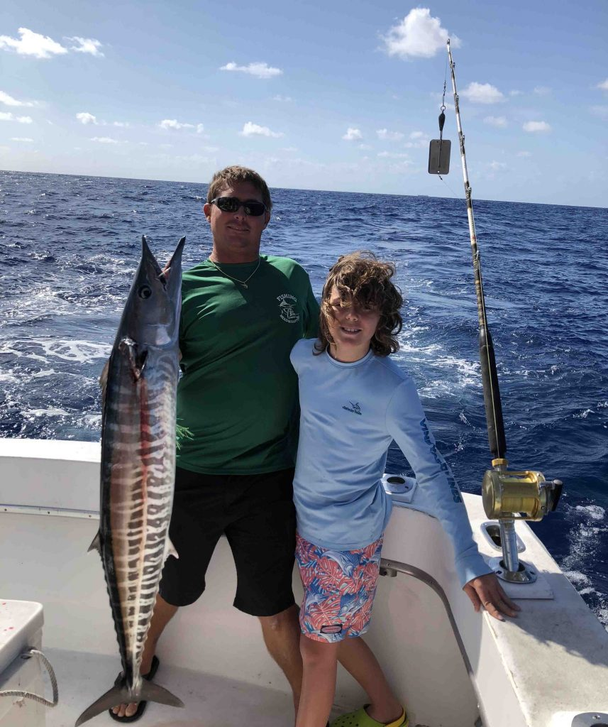 Capt Rod and the angler posing with a big wahoo they just caught trolling the reef.