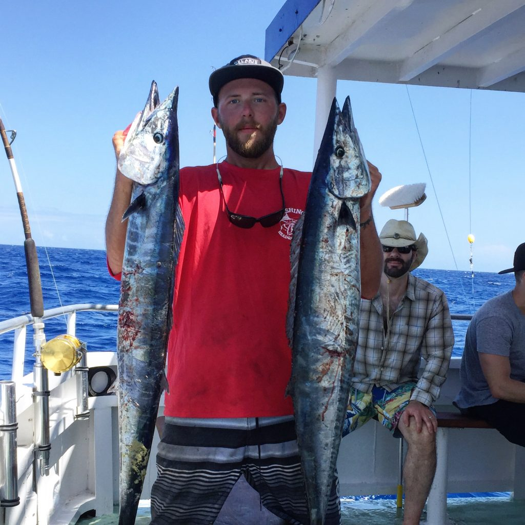 Josh holding a pair of wahoo caught on a bachelor party fishing trip out of Fort Lauderdale