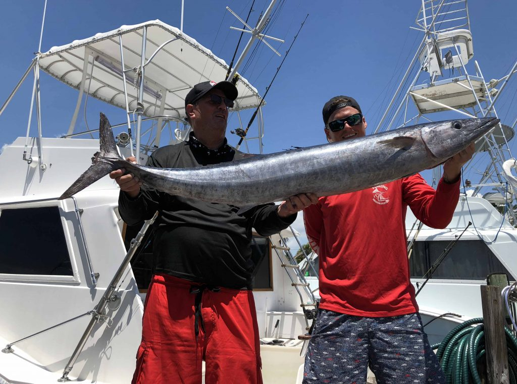 2 guys holding up a big wahoo at the dock in Fort Lauderdale.