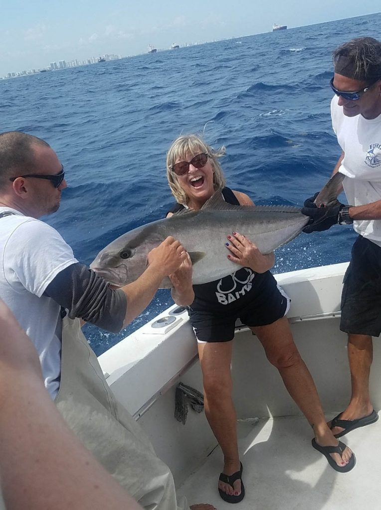 A very happy gal holding a 40 pound amberjack during her deep sea fishing charter