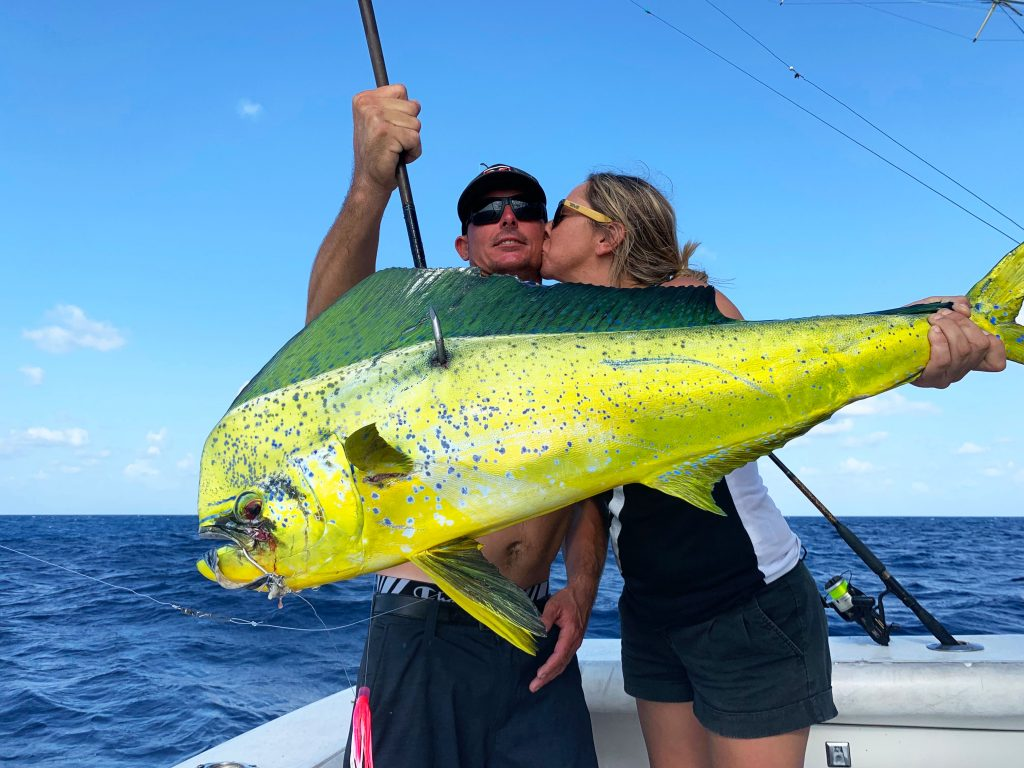 Mahi-mahi dolphin being held on the gaff, girl kissing captain holding it