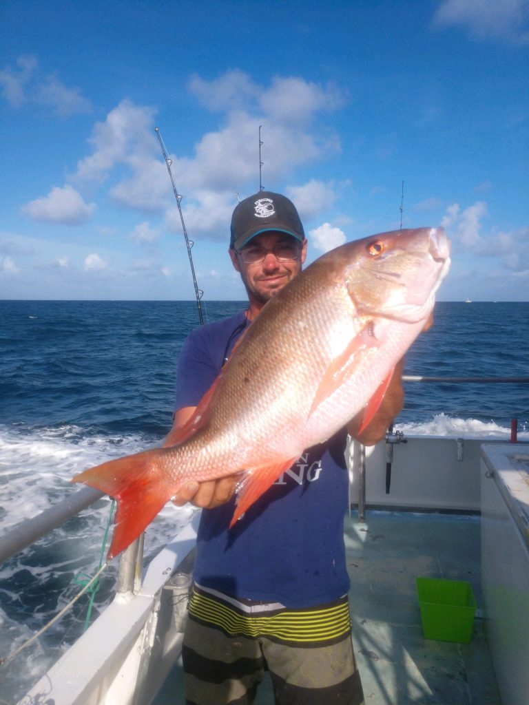 Ryan holding a big mutton snapper he just caught fishing aboard the Catch My Drift with a beautiful ocean and sky in the background.