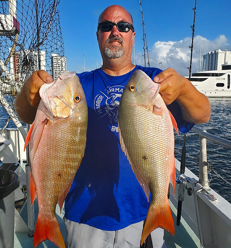 Ryan holding a pair of mutton snappers up while aboard the Catch My Drift with the Bahia Mar marina and yachts in the background
