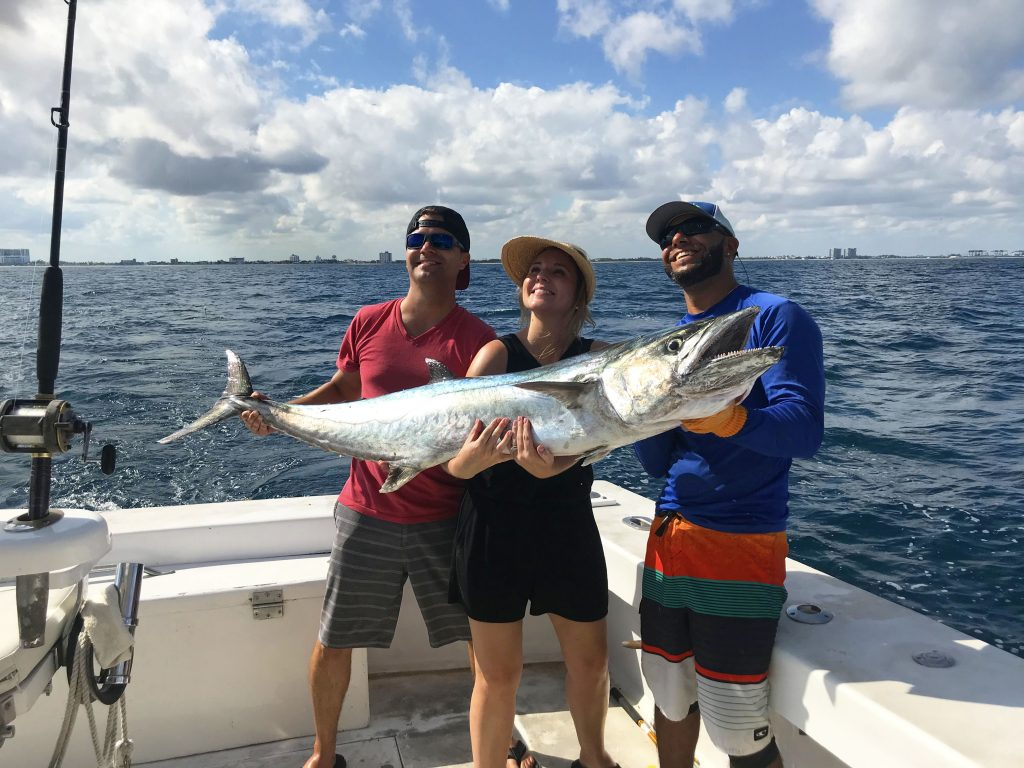 Bobby and couple on vacation posing with their huge kingfish, just caught offshore Ft Lauderdale beach