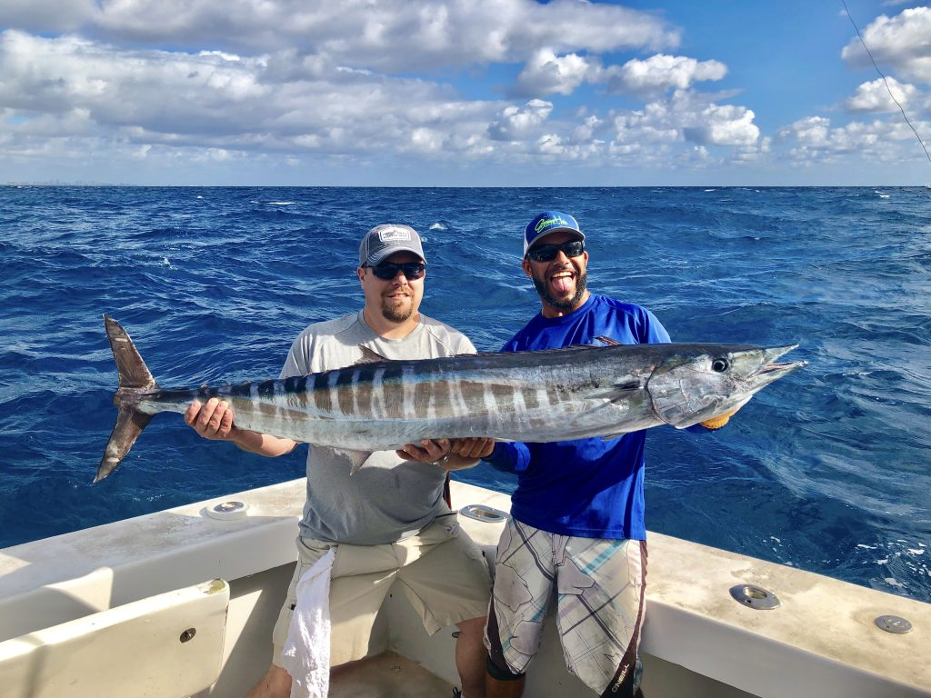 Capt Bobby holding a 50 pound wahoo in the boat with the happy angler who caught it. Beautiful sky in the background amidst a choppy ocean.